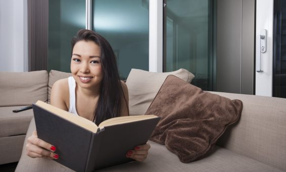 Portrait of happy woman reading book while lying on sofa